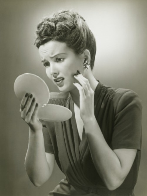 A woman staring into her mirror with a frightened look.